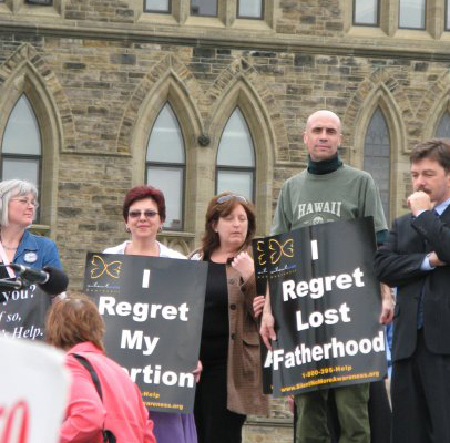 Hugh holding abortion sign, Silent No More, Canadian Parliament